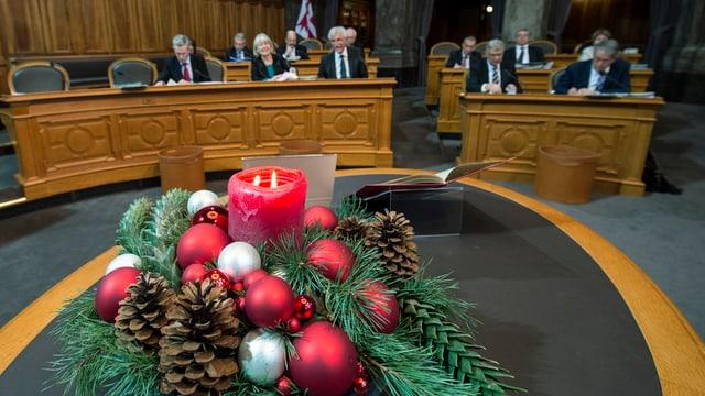 Adventskranz mit einer dicken Kerze mit zwei brennenden Dochten auf einem Tisch in der Mitte des Ständerats.