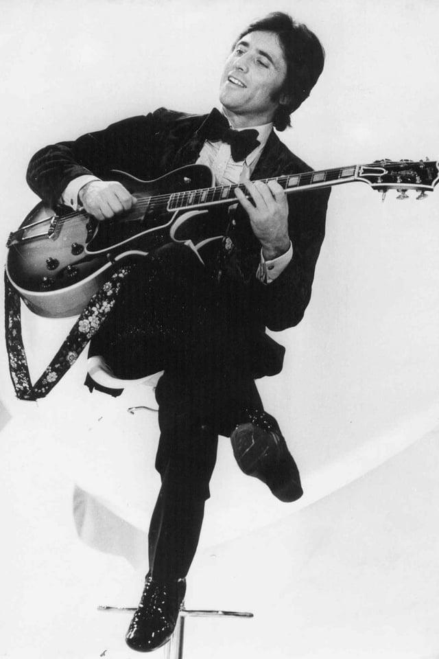 Schwarzweissfoto von Distel auf Stuhl sitzend und mit Gitarre