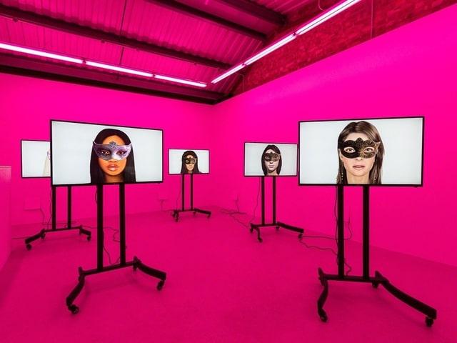Ein rosa erleuchteter Raum mit fünf Bildschirmen, darauf sind Avatare von Frauen mit Augenmasken zu sehen.