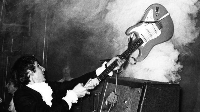 Ein junger Mann im schwarzen Anzug schlägt seine Gitarre auf einen rauchenden Verstärker.