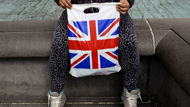 Eine Frau hält einen Plastiksack, auf dem die britische Flagge zu sehen ist.