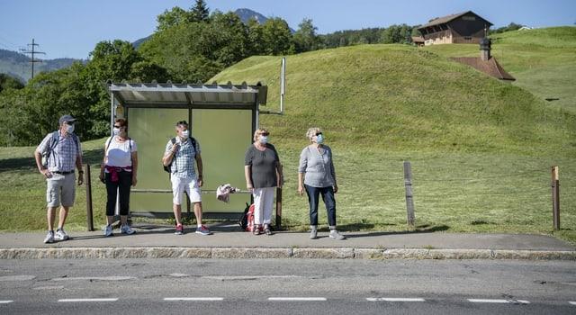 Personen warten in ländlicher Umgebung auf einen Bus – alle tragen Hygienemasken.