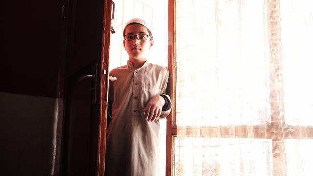 Junge mit Brille in einer Tür.