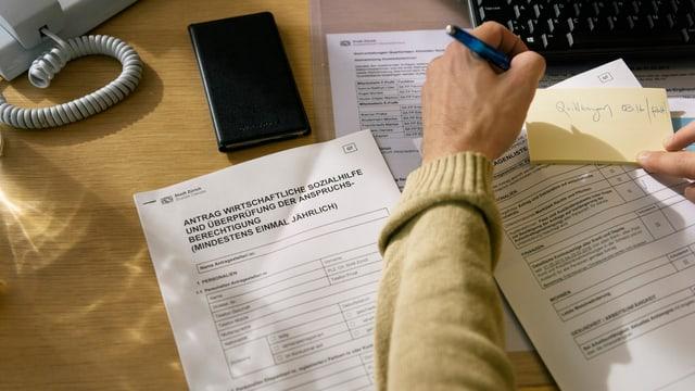 Arm einer Person, in der Hand ein Kugelschreiber, daneben Formulare der Sozialhilfe