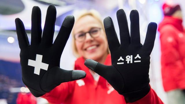 Frau, lachend, streckt die Hände vor, Handschuhe mit fremden Schriftzeichen