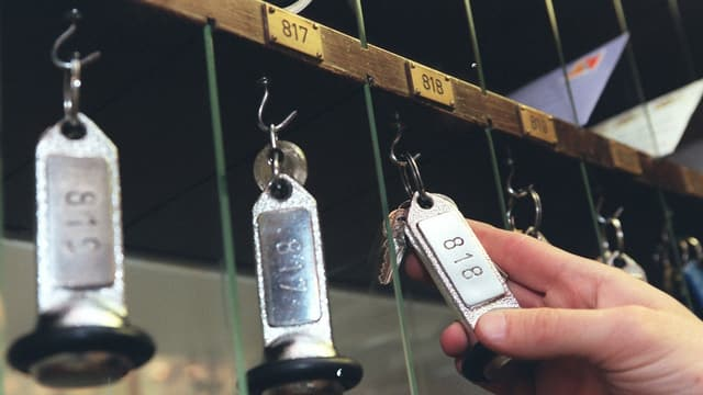 Eine Hand nimmt einen Hotelschlüssel von eibnem Haken.