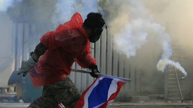 Person mit Gesichtsmaske vor Rauchschwaden
