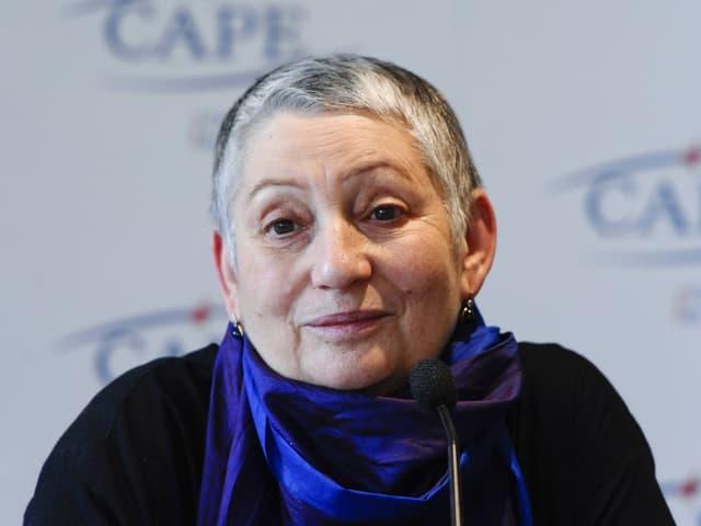 EIne Frau mit kurzen, grauen Haaren und dunkelblauem Seidenschal.