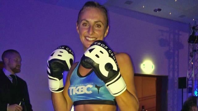 Eine Frau mit Boxhandschuhen.