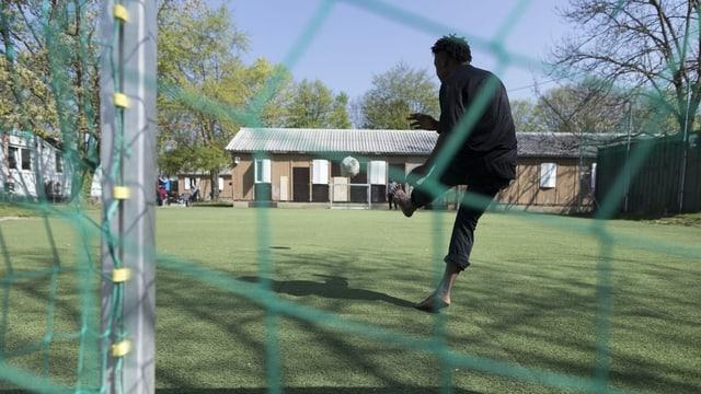 Ein Mann spielt Fussball vor der Asylunterkunft Juch in Zürich.
