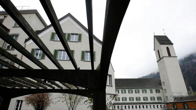 Das weisse Schulgebäude mit Kirchturm an einem grauen Tag.