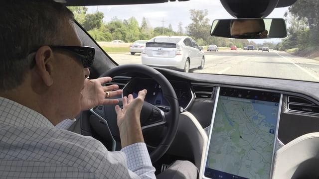 Blick durch die Frontscheibe eines fahnrenden Teslas, der Lenker gestikuliert und hat die Hände nicht am Steuer