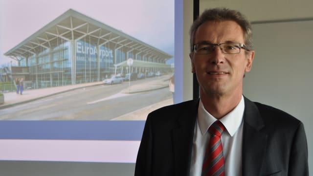 Matthias Suhr steht vor einer Abbildung des EuroAirport.