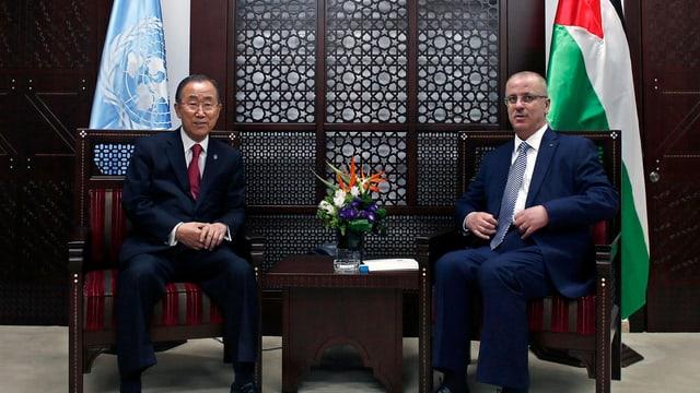 Ban Ki Moon (links) und Rami Hamdallah (rechts) sitzen nebeneinander unter einer UNO- und einer Palästinenser-Flagge