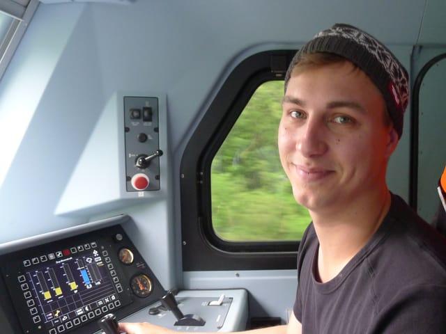 Der junge blondharige Lokführer mit einer Kappe auf dem Kopf sitzt vorne im Führerstand der Lokomotive.