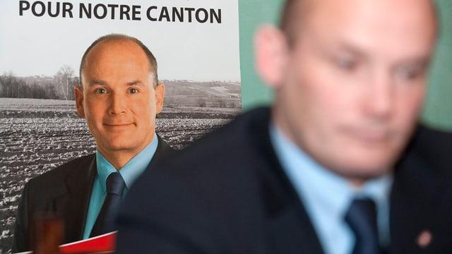 Yvan Perri unscharf im Vordergrund, ein Plakat von ihm, scharf, im Hintergrund.