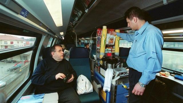 Stewart mit Minibar bedient einen Zugpassagier