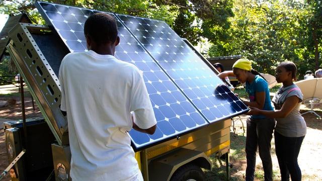 Menschen, die Solarpanel von einem Anhänger hieven.