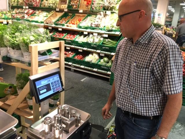 Der Eichmeister legt verschiedene Gewichte auf eine Gemüsewaage.
