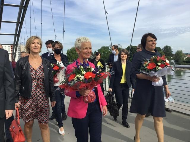 Leute gehen feierlich über Dreiländerbrücke.