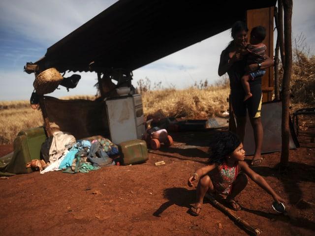 Eine Frau mit zwei kleinen Kindern unter einem Wellblechunterstand.