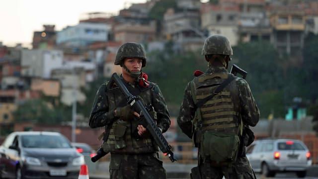Zwei Soldaten patroullieren bewaffnet auf einer Strasse.