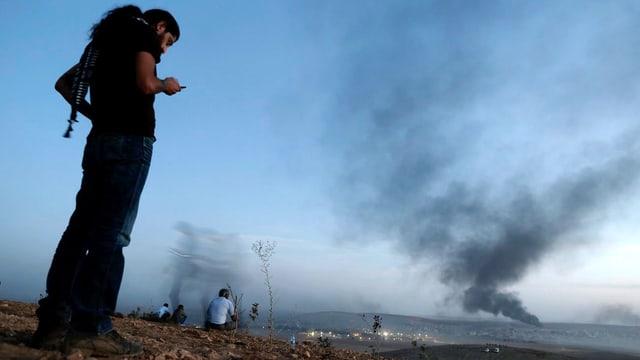 Ein Mann in Schwarz steht am linken Bildrand und schaut in sein Handy, im Hintergrund Felder, von denen Rauch hochsteigt.