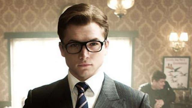 Ein junger Mann mit Brille, der einen Anzug trägt in einem Pub.