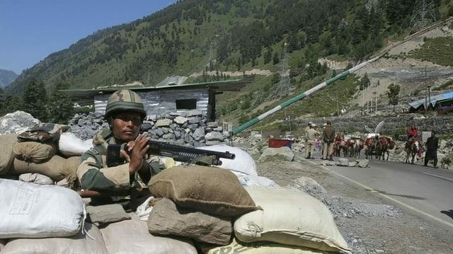Ein Checkpoint mit Sandsäcken und einem bewaffneten Grenzsoldaten