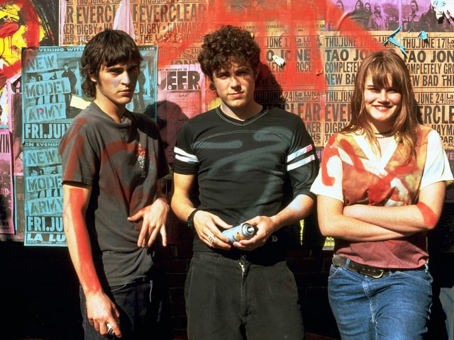Joaquin Phoenix, Casey Affleck, Allison Folland stehen mit Spraydosen vor einer Wand.