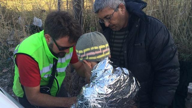Ein Mann kleidet einen Jungen mit einer Rettungsdecke ein
