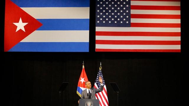 Obama am Rednerpult im Hintergrund die Flaggen von USA und Kuba.