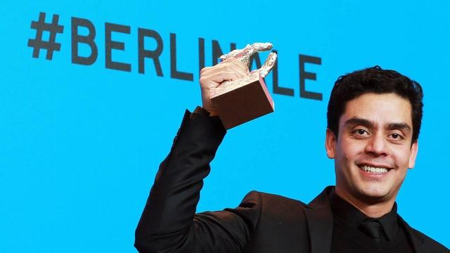 Lächelnder Mann hält eine Auszeichnung in die Höhe.