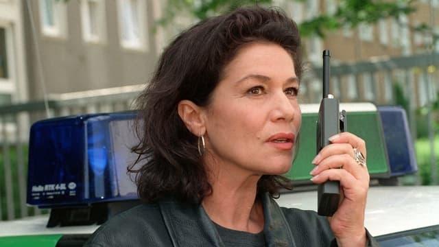 Purtret da Hannelore Elsner durant filmar la seria «Die Kommissarin». Ella tegn in func enta maun, davos ella è da vesair in auto da polizia tudestg. Ella porta ina giacca da curom naira.