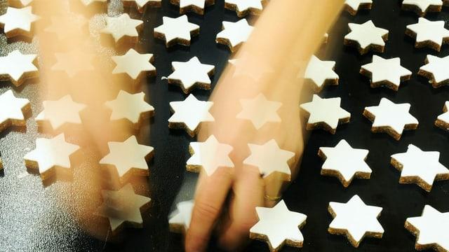 Zwei Hände ordnen Zimtsterne auf einem Backblech an.