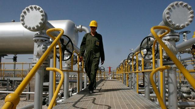 Ein Mann mit einer Schutzkappe geht über eine Ölförderanlage an Rohren vorbei.