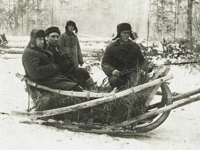 Drei Männer auf einem Schlitten, gefüllt mit Stroh. Im Hintergrund geht ein weiterer Mann.