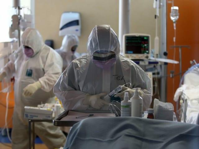 Menschen in Schutzanzügen im Spital.