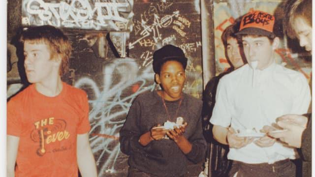 """Fünf Buben stehen vor einer besprayten Wand und essen Kuchen. Einer trägt eine Baseballmütze mit der Aufschrift """"Beastie Boys""""."""