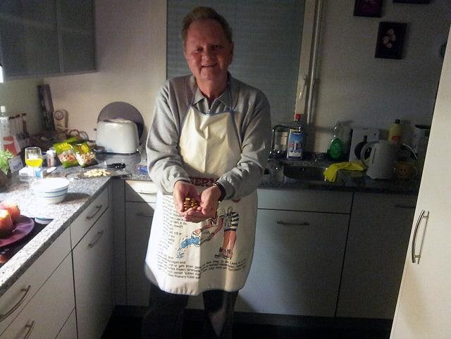 Ein Mann mit Küchenschürze zeigt eine Handvoll Mandeln.