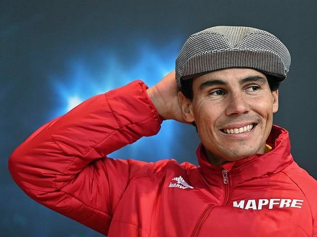 Rafael Nadal trägt eine Schildmütze und lächelt