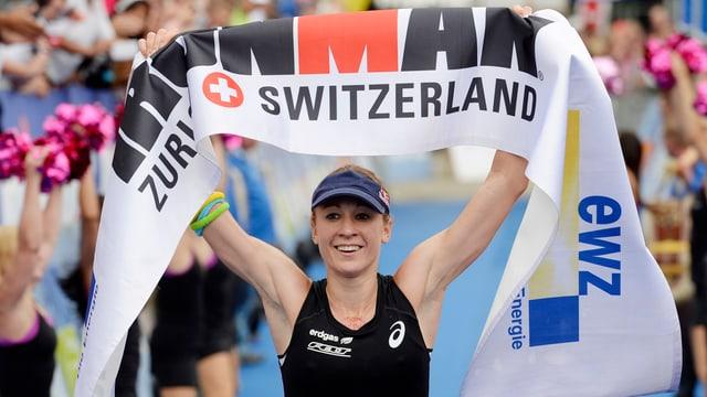 Eine Frau hebt ein Banner mit der Aufschrift Ironman über den Kopf.