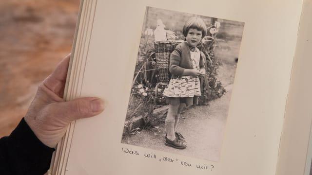 Blick in ein Fotoalbum: Eine Schwarz-Weiss-Aufnahme zeigt ein kleines Mädchen mit einem Korb auf dem Rücken.