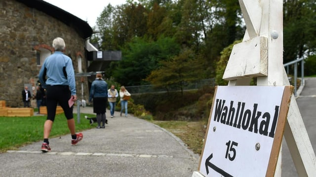 Personen gehen in ein Wahllokal ihre Stimme abgeben