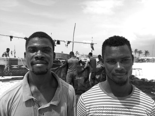 Schwarz-Weiss-Aufnahme: Porträtaufnahme der beiden Männer. Im Hintergrund hängen Fischer ein langes Netz an ein Boot.
