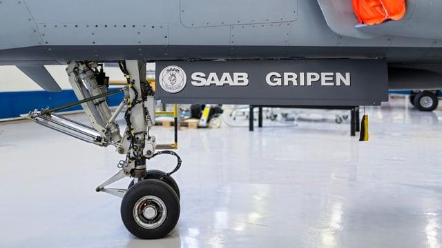 Die Räder eines Gripen, der in einem Hangar steht.