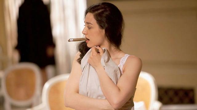 Eine Frau bedeckt ihren Körper mit einem Tuch. Sie hat eine Zigarre im Mund.