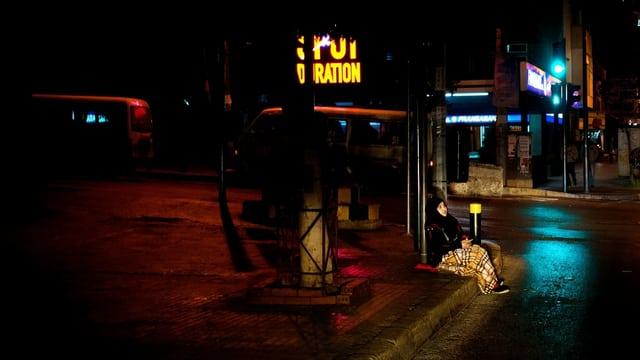 Obdachlose Frau in der Dunkelheit, sie sitzt am Strassenrand.