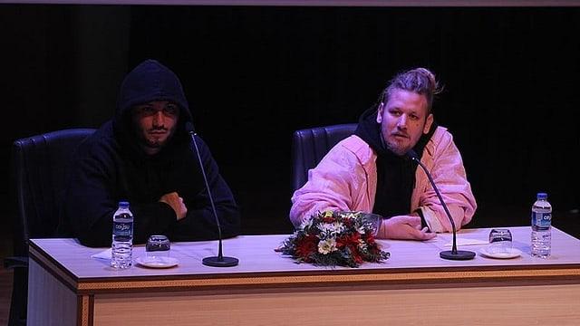 Zwei Männer vor Mikrofonen.