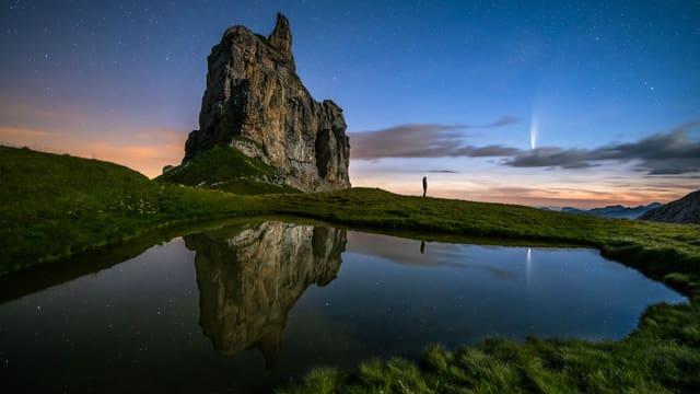 Blick in der Nacht über Bergsee. Dahinter Fels und fast klarer Himmel mit einem Kometen.